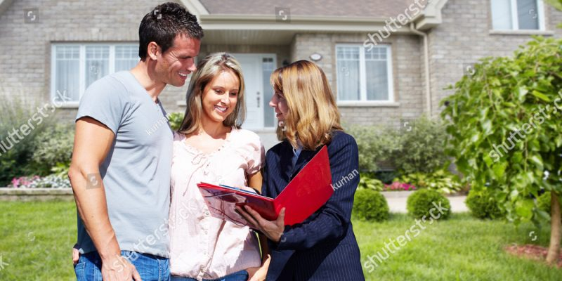 stock-photo-real-estate-agent-woman-with-clients-near-new-house-432517339